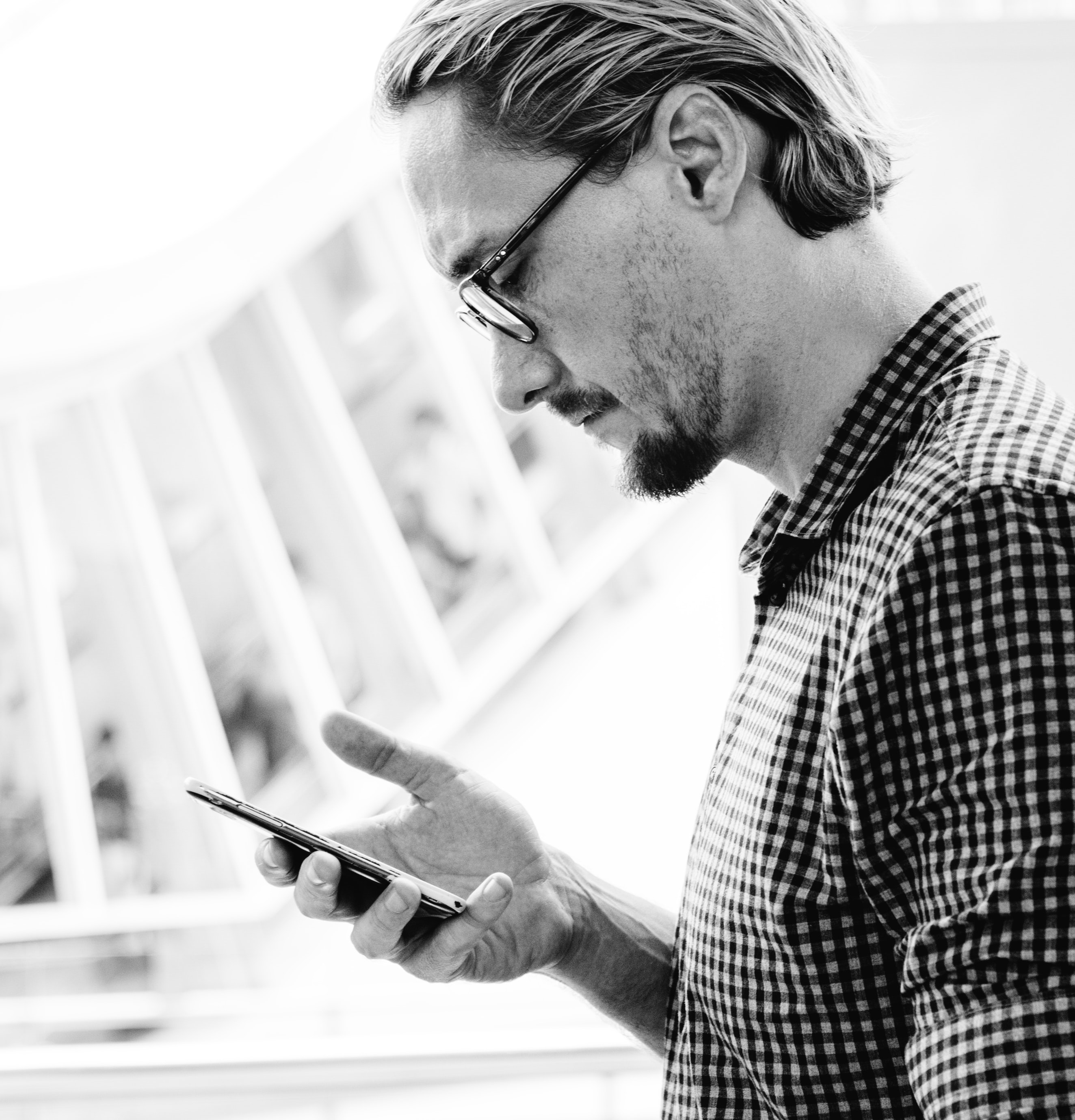 grayscale photo of man holding smartphone