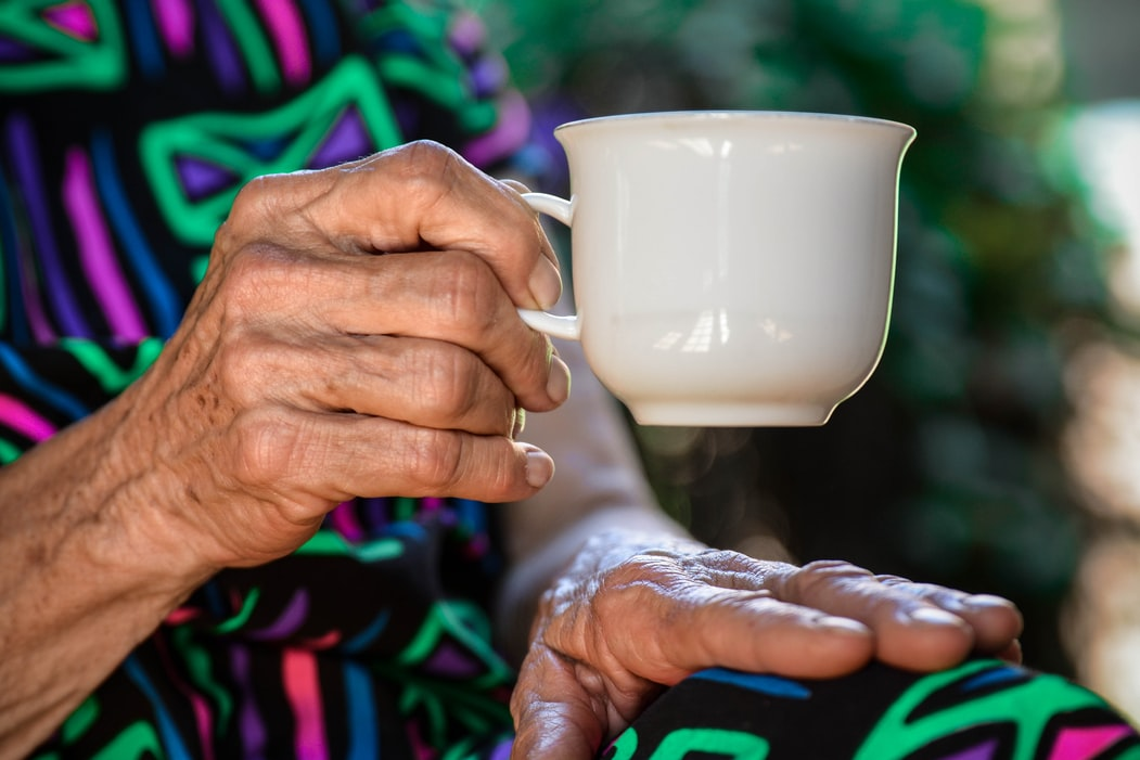old hands holding a coffee cup