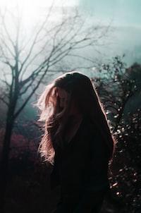 woman in black coat standing