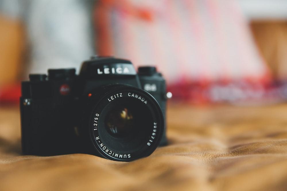 black Leica DSLR camera on brown surface