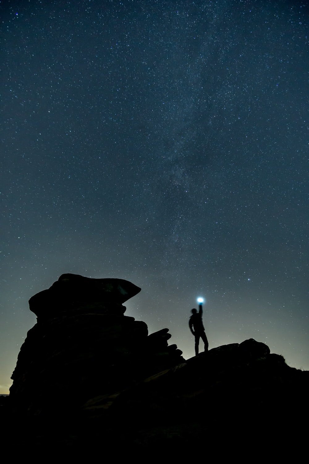 silhouette photo of man at top of mountain