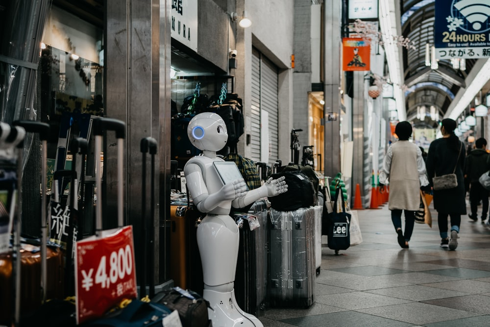 robot standing near luggage bags