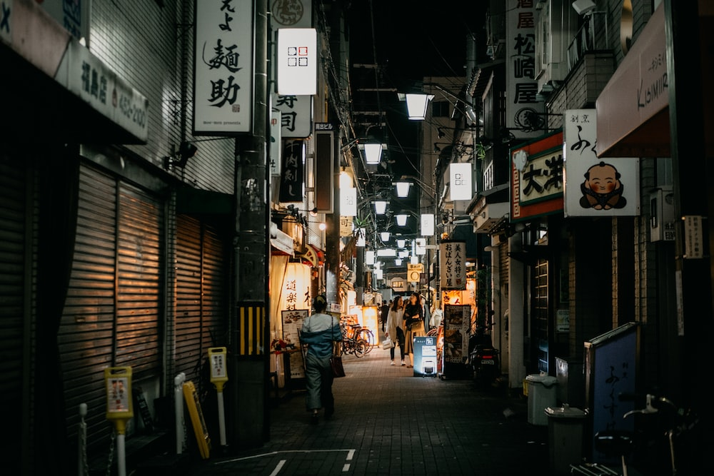 person walking in alley with signs