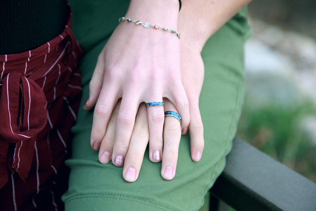 A young couple showing their non-traditional blue engagement rings. They have set a wedding date in May of 2019.