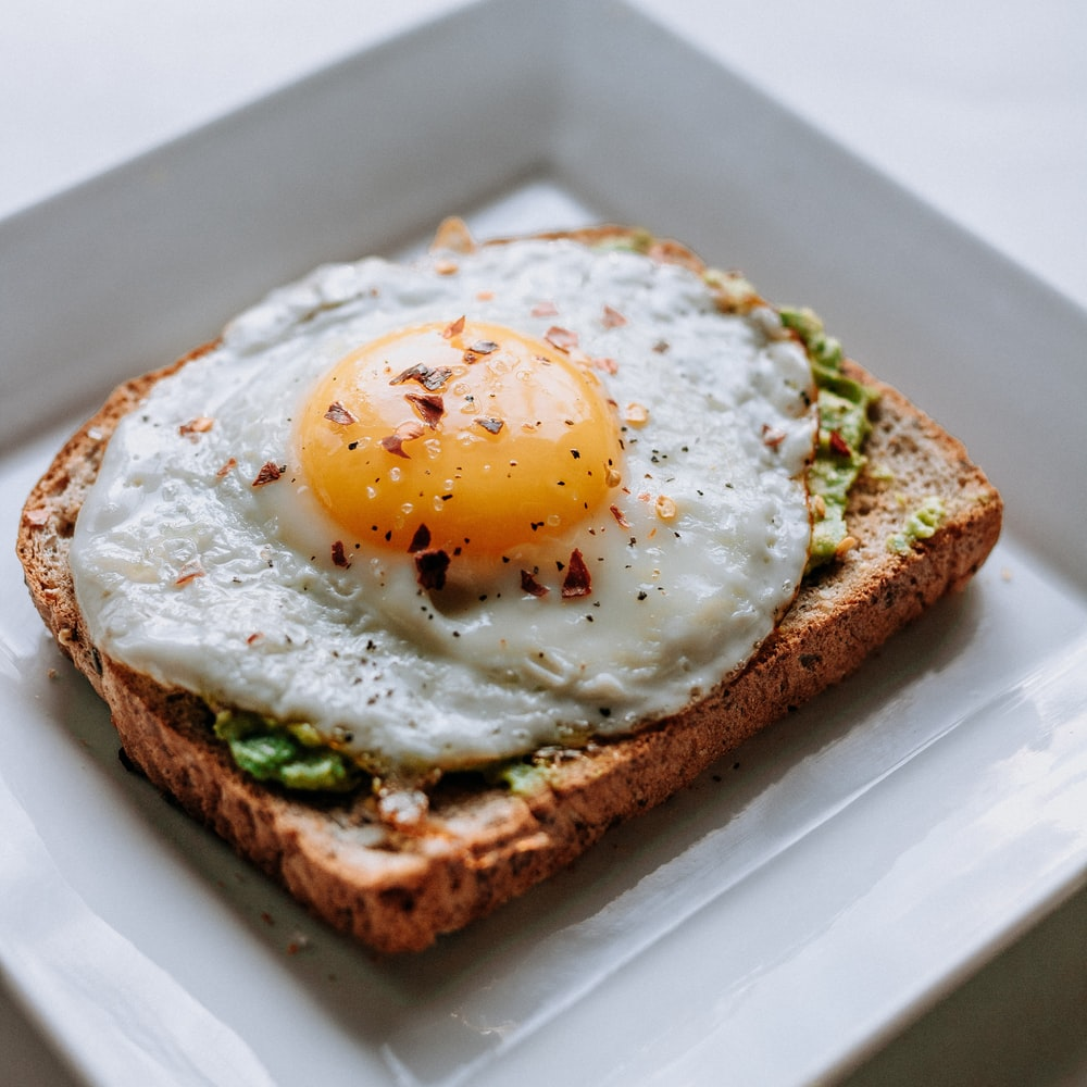 bread with sunny side-up egg served on white ceramic plate