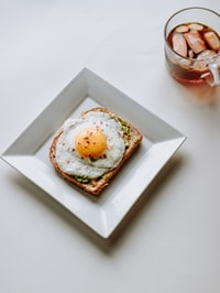 fried egg white ceramic plate beside glass mug