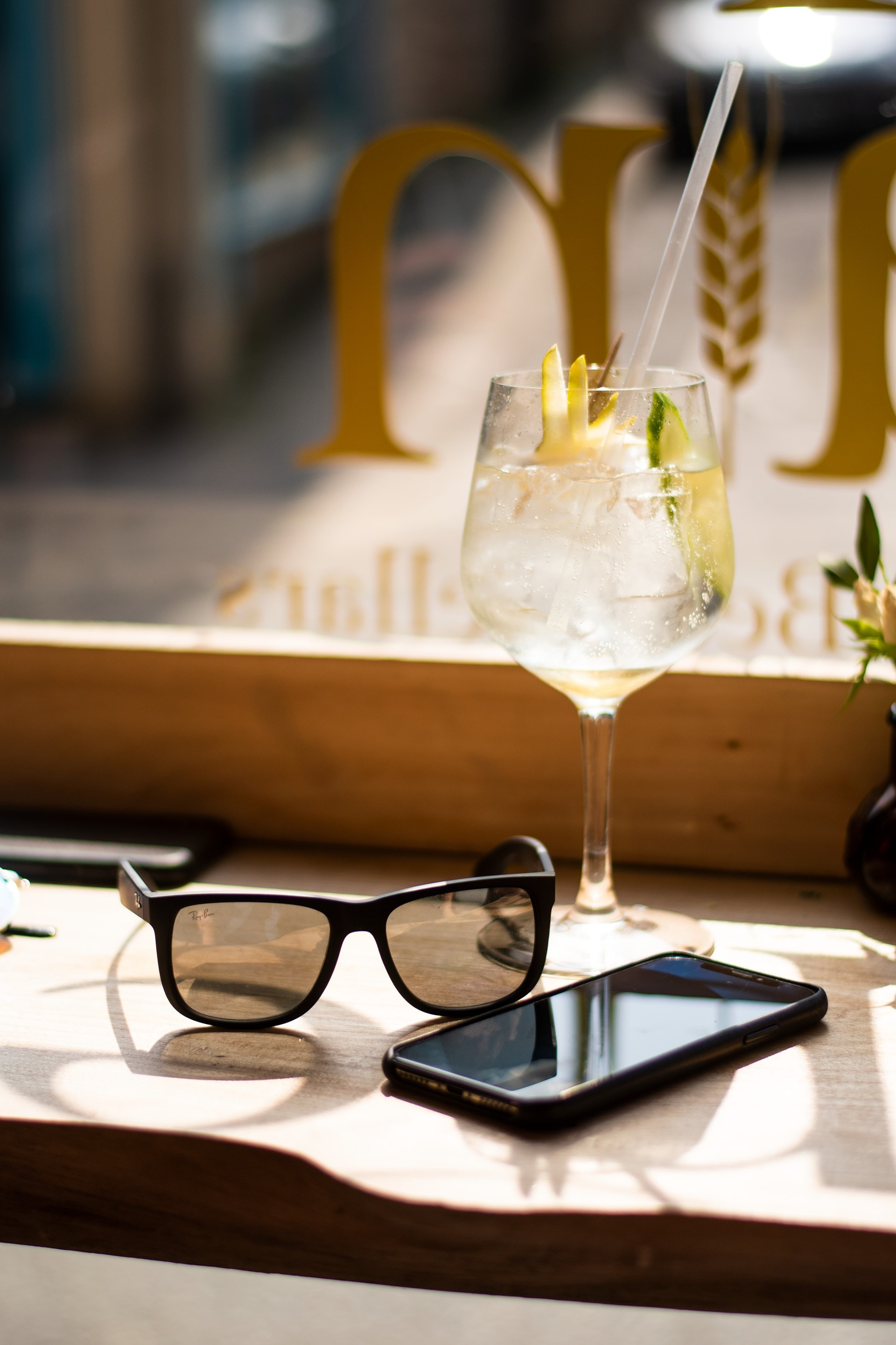 smartphone, wayfarer sunglasses, and wine glass on tray