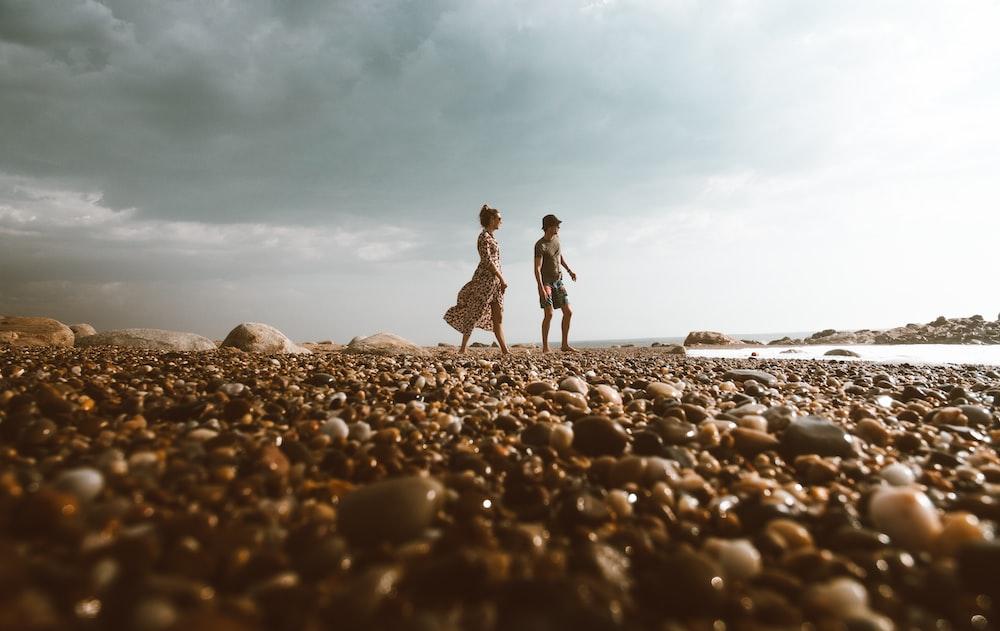 man and woman walking on stones near beach under blue sky