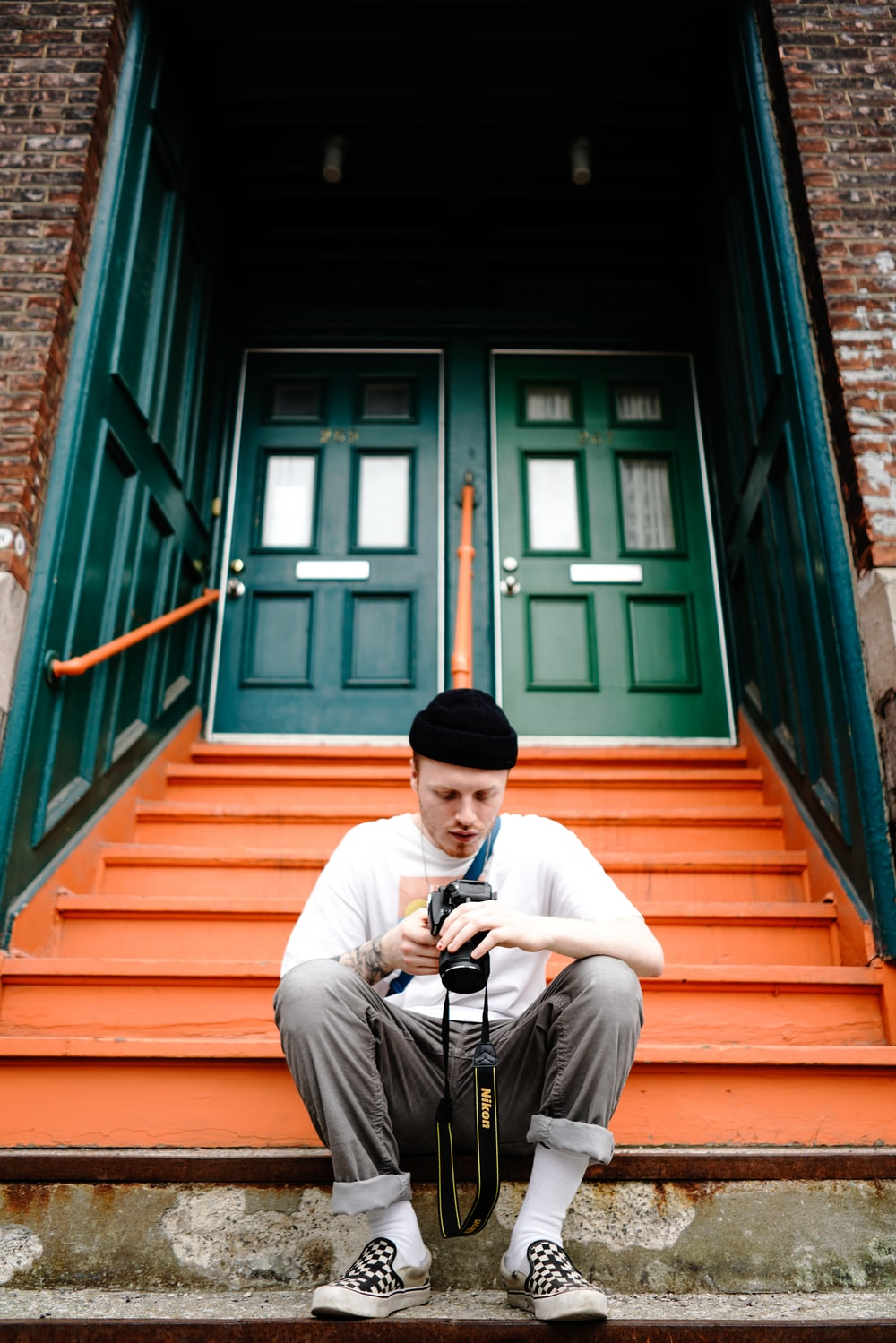 man seating in front of stair while holding DSLR camera