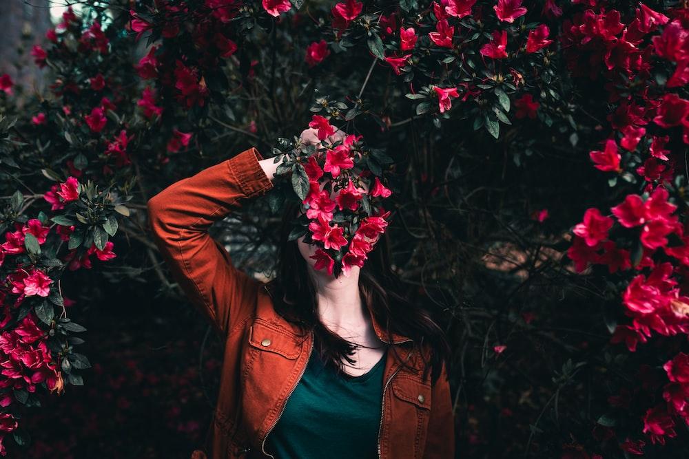 woman holding flower standing near flowers