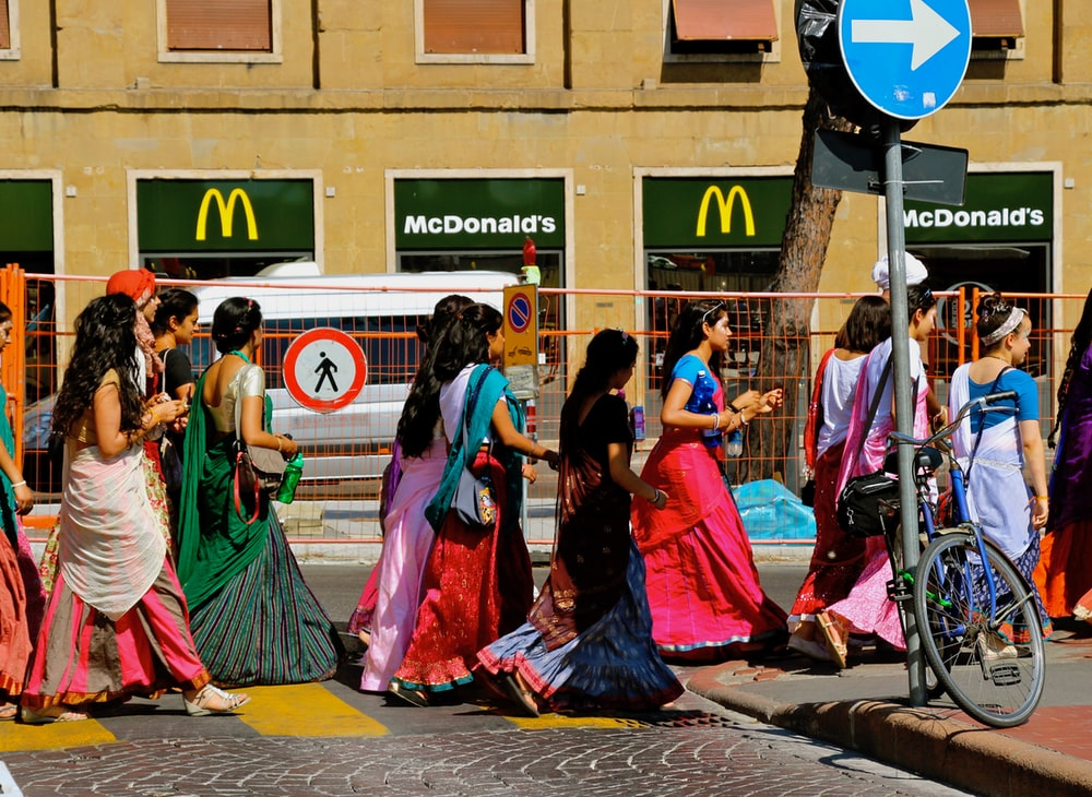 women in traditional dresses walking on street in Italy