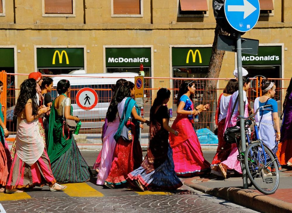 women in traditional dresses walking on street