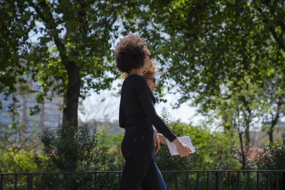two women walking near trees at daytime
