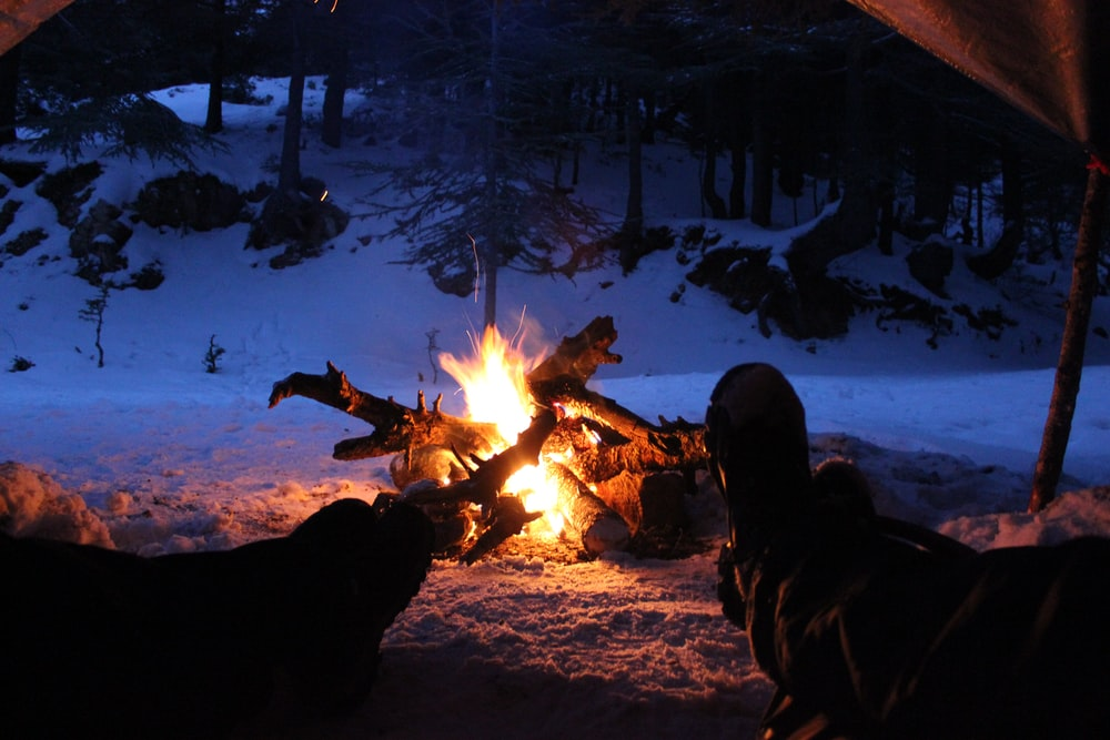 person sitting in front of bonfire
