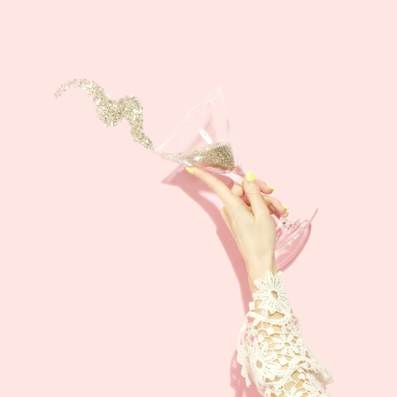 A pink background with a woman's hand holding a clear martini glass full of glitter, with some spilled out.