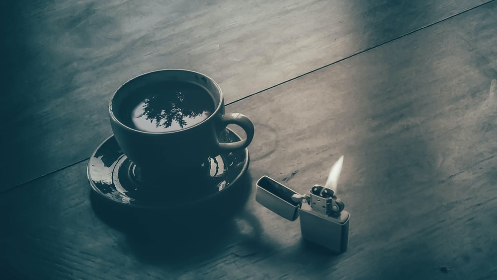 white ceramic tea cup on saucer near gray flip lighter