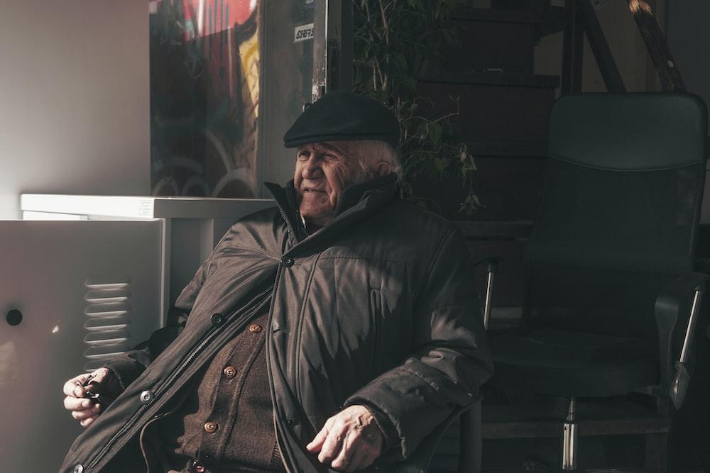 man sitting on black chair during daytime