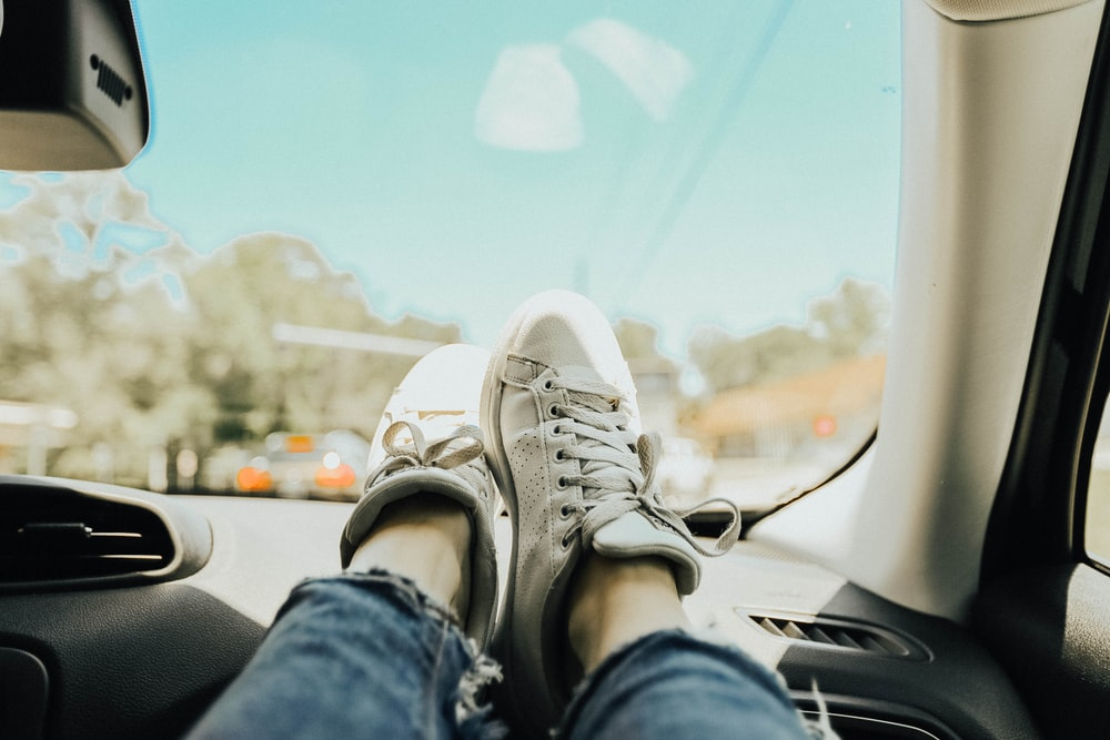 person resting feet on car dashboard