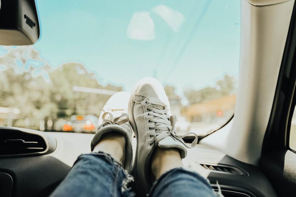 person resting feet on car dashboard