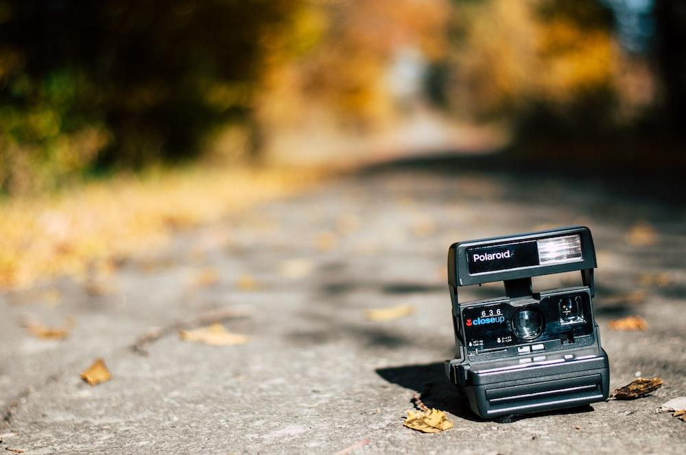 selective focus photography of black Polaroid land camera on land