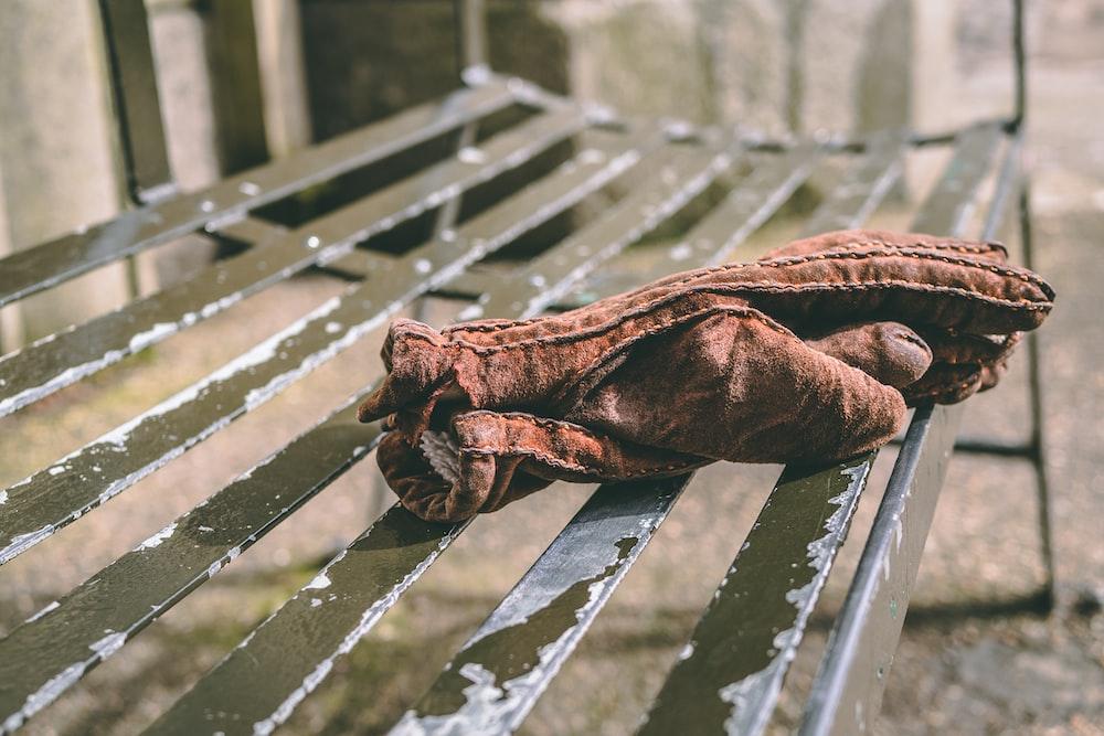 pair of brown mittens on black metal bench