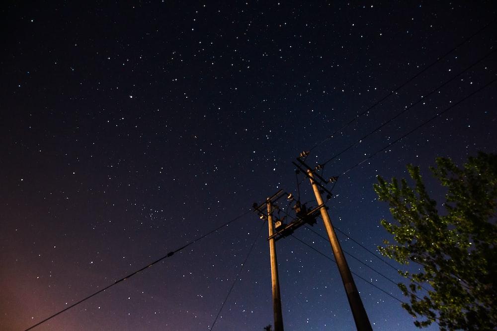 two gray street posts under dark sky