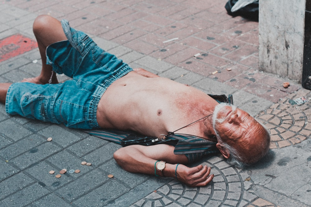 topless man lying on brick pavement