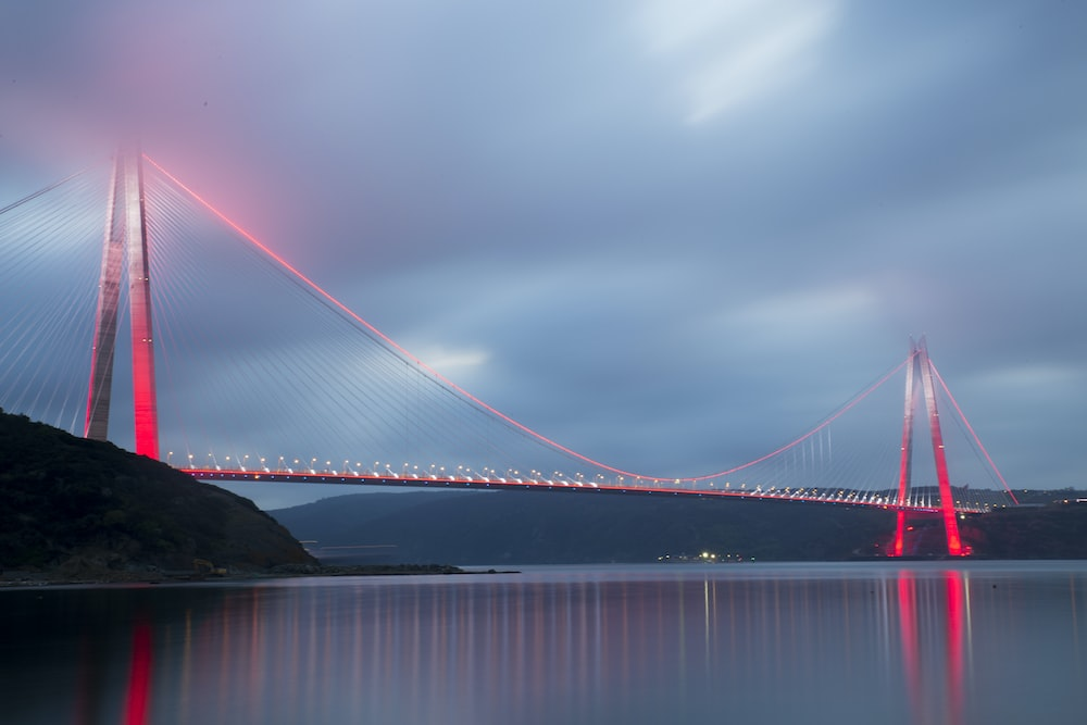 gray concrete bridge with red LED light above calm water