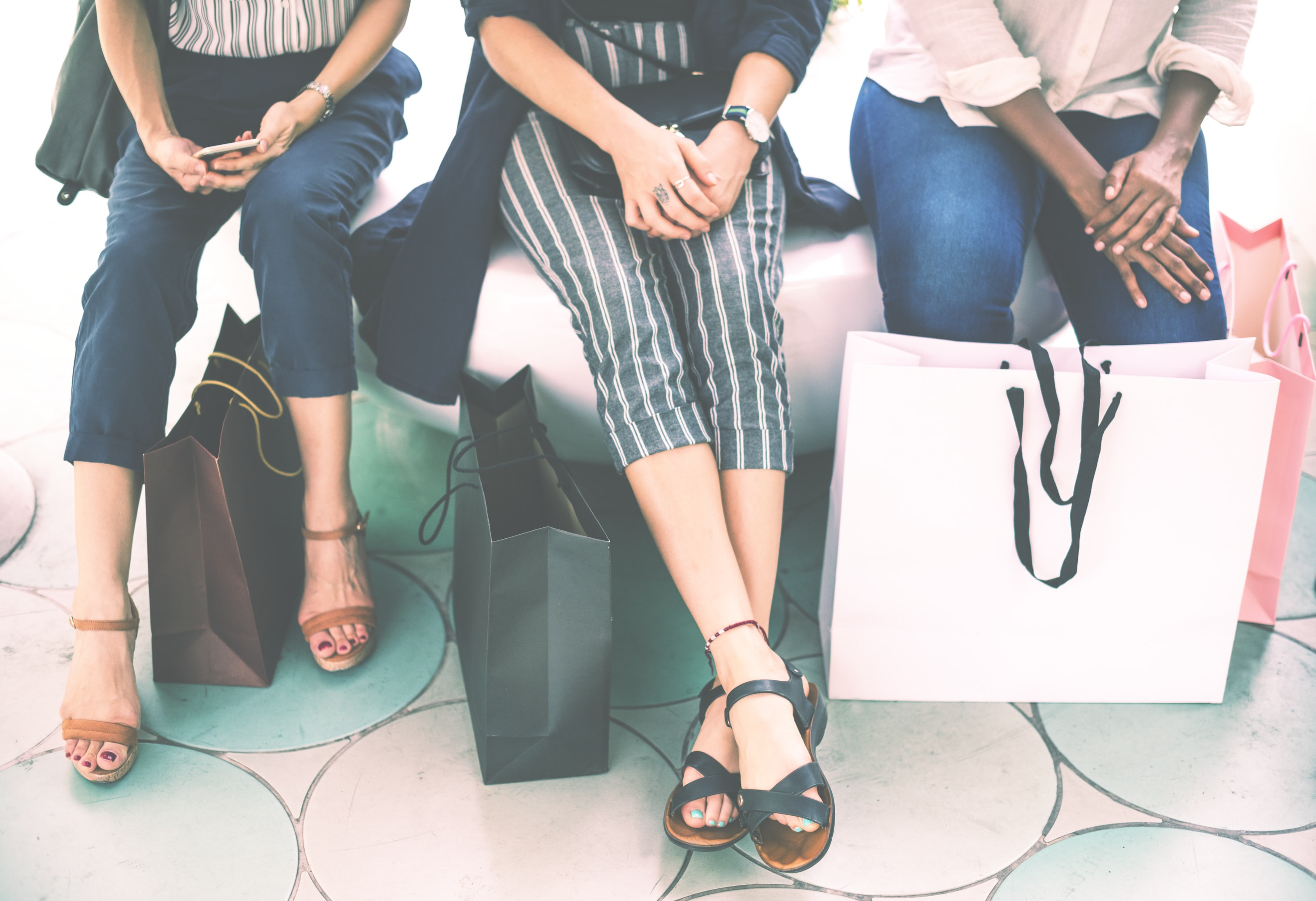 three woman beside paper bags