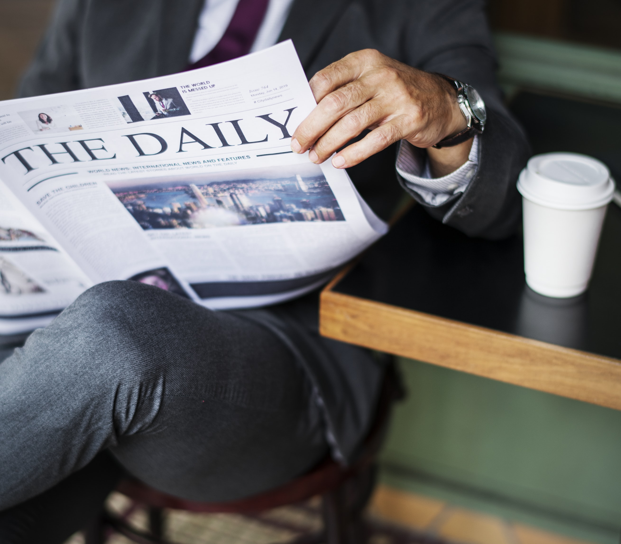man sitting while reading newspaper beside table