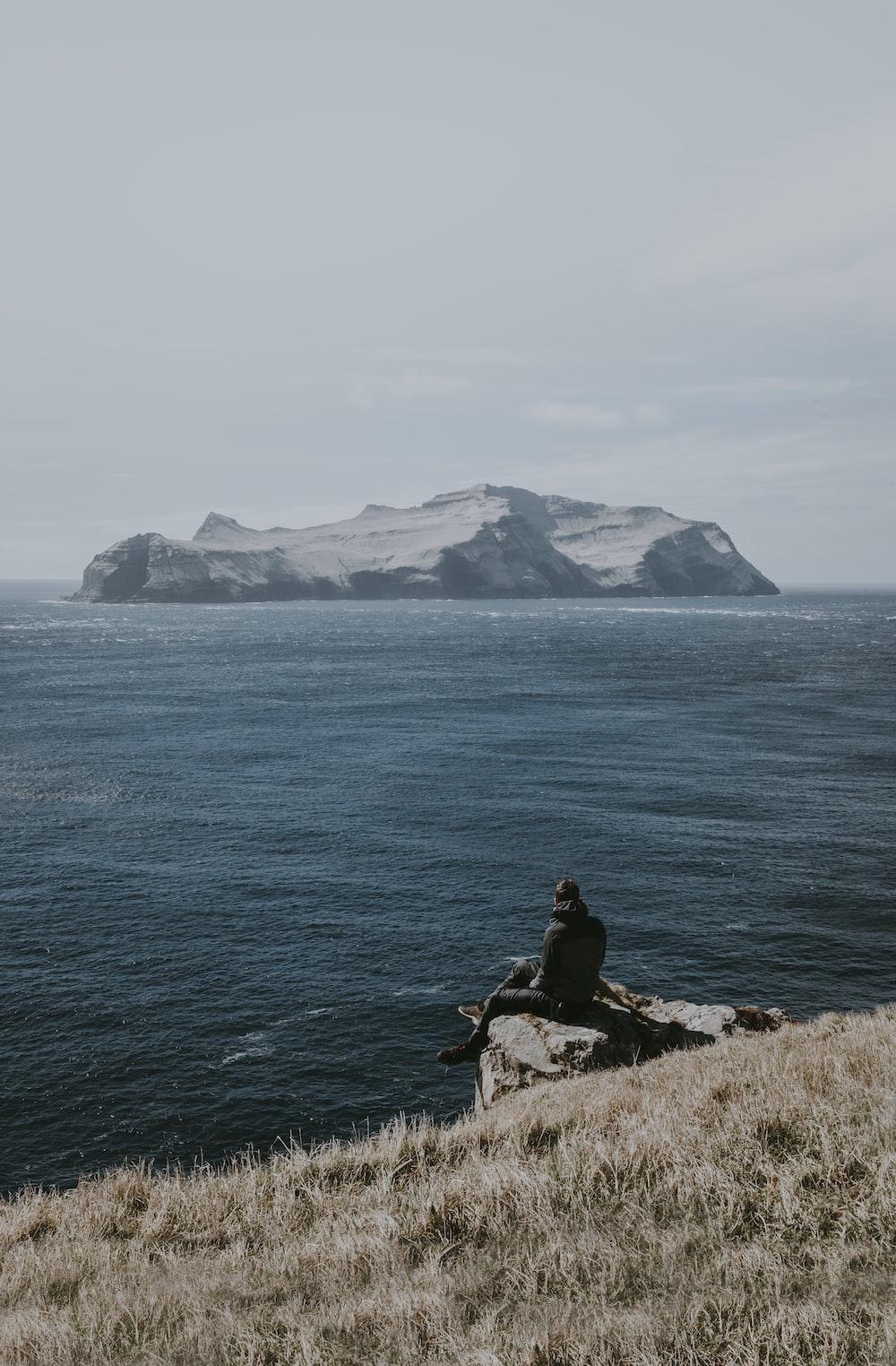 man sitting on rock formation beside sea