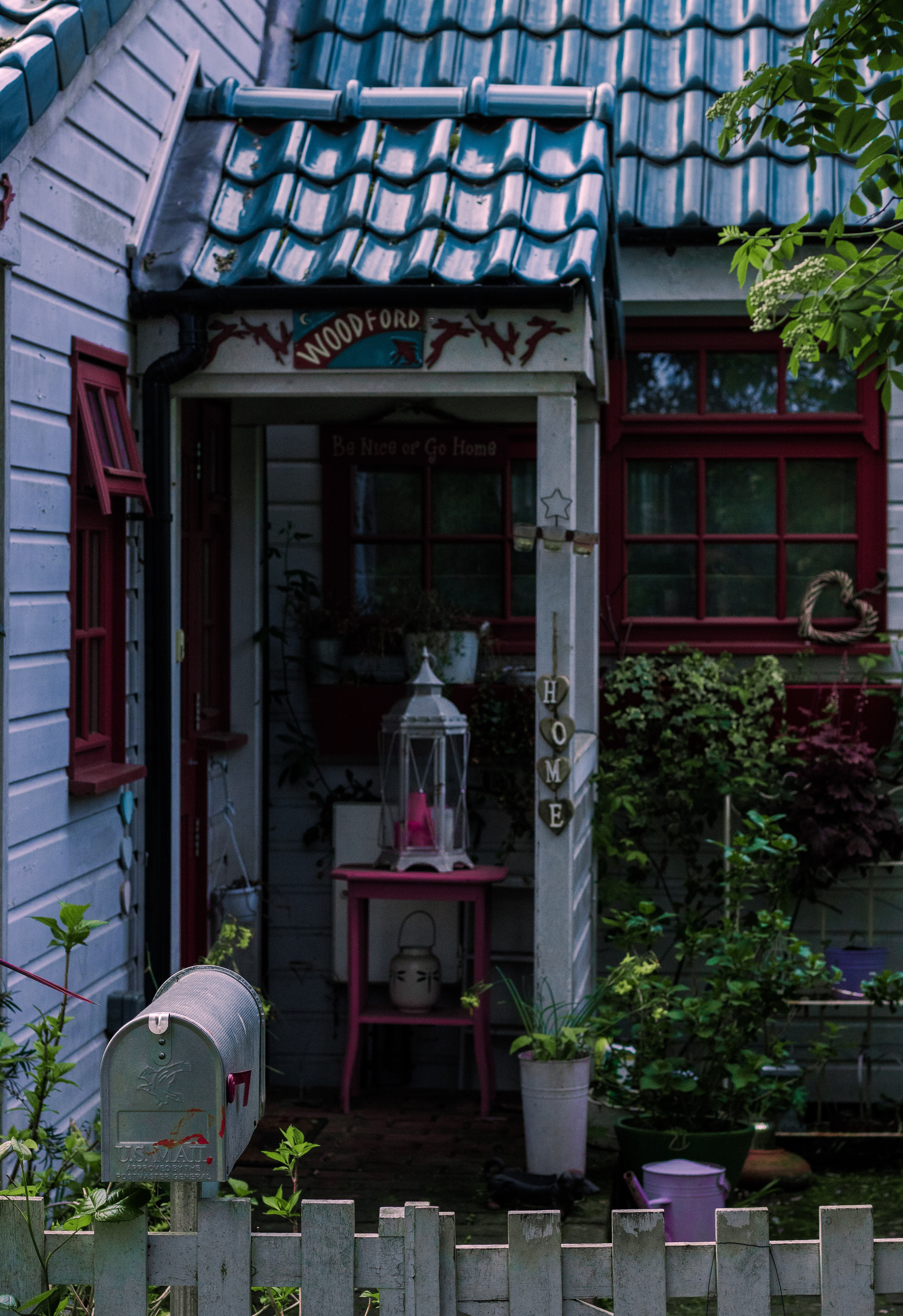 gray metal framed lantern on pink wooden table outside house