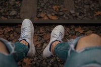 sitting person in front of railway wearing distressed blue fitted jeans and pair of white low-top sneakers