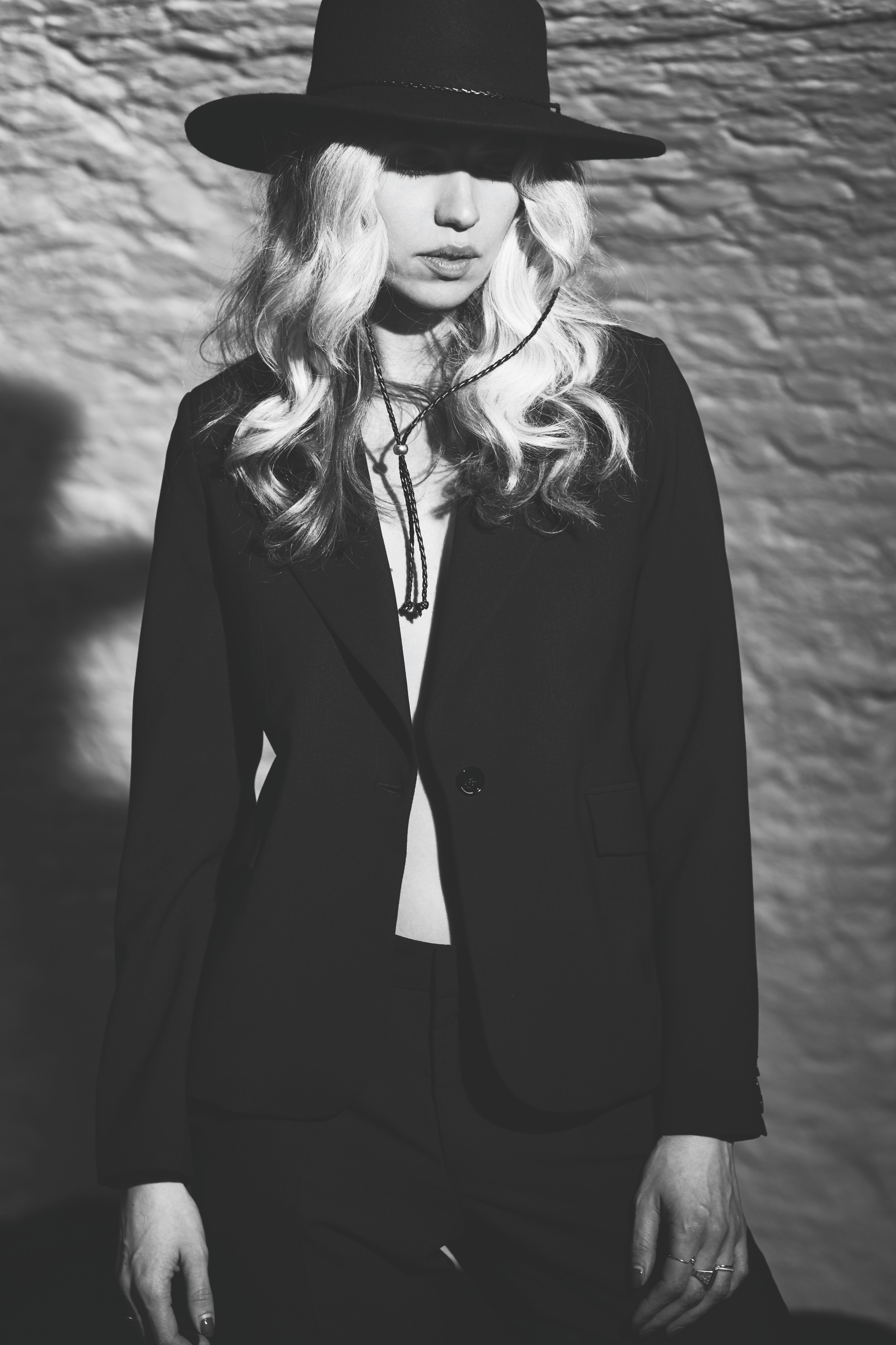 grayscale photography of woman in suit wearing hat