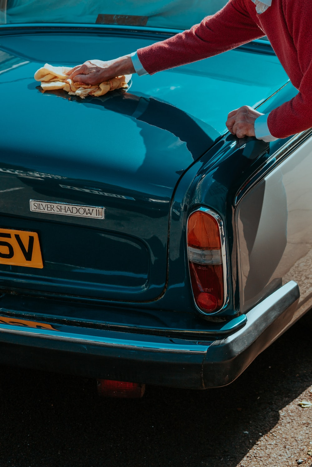 man cleaning vehicle trunk lid at daytime