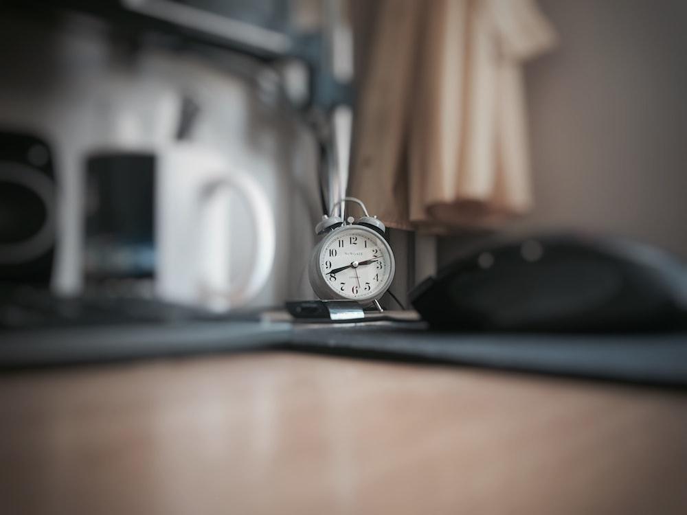 round grey alarm clock at 2:40