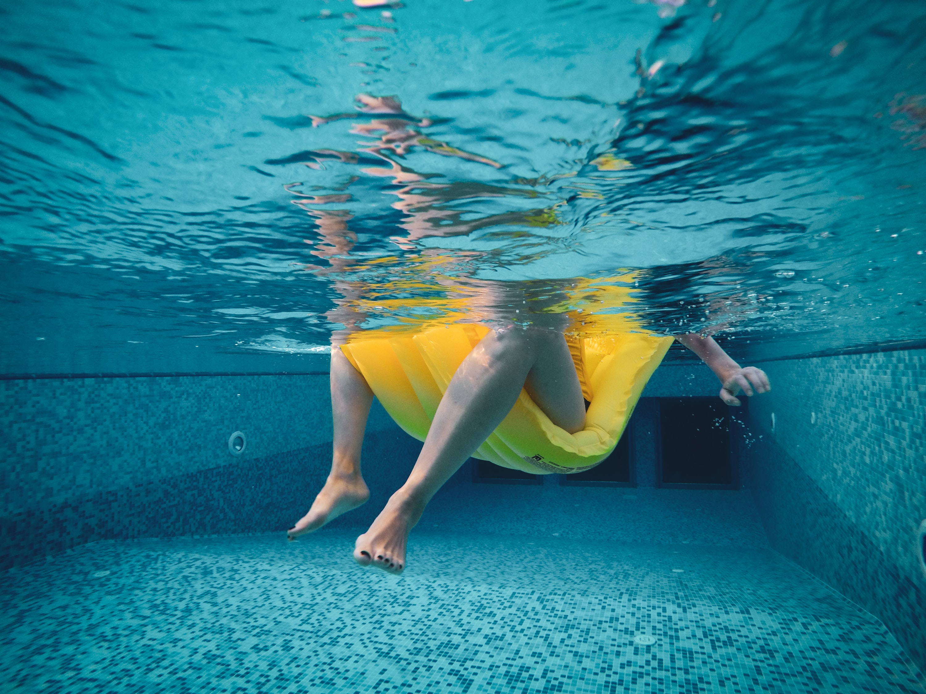 woman on yellow float sinking in swimming pool