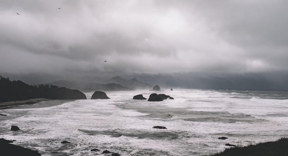rock formations between sea under gray sky