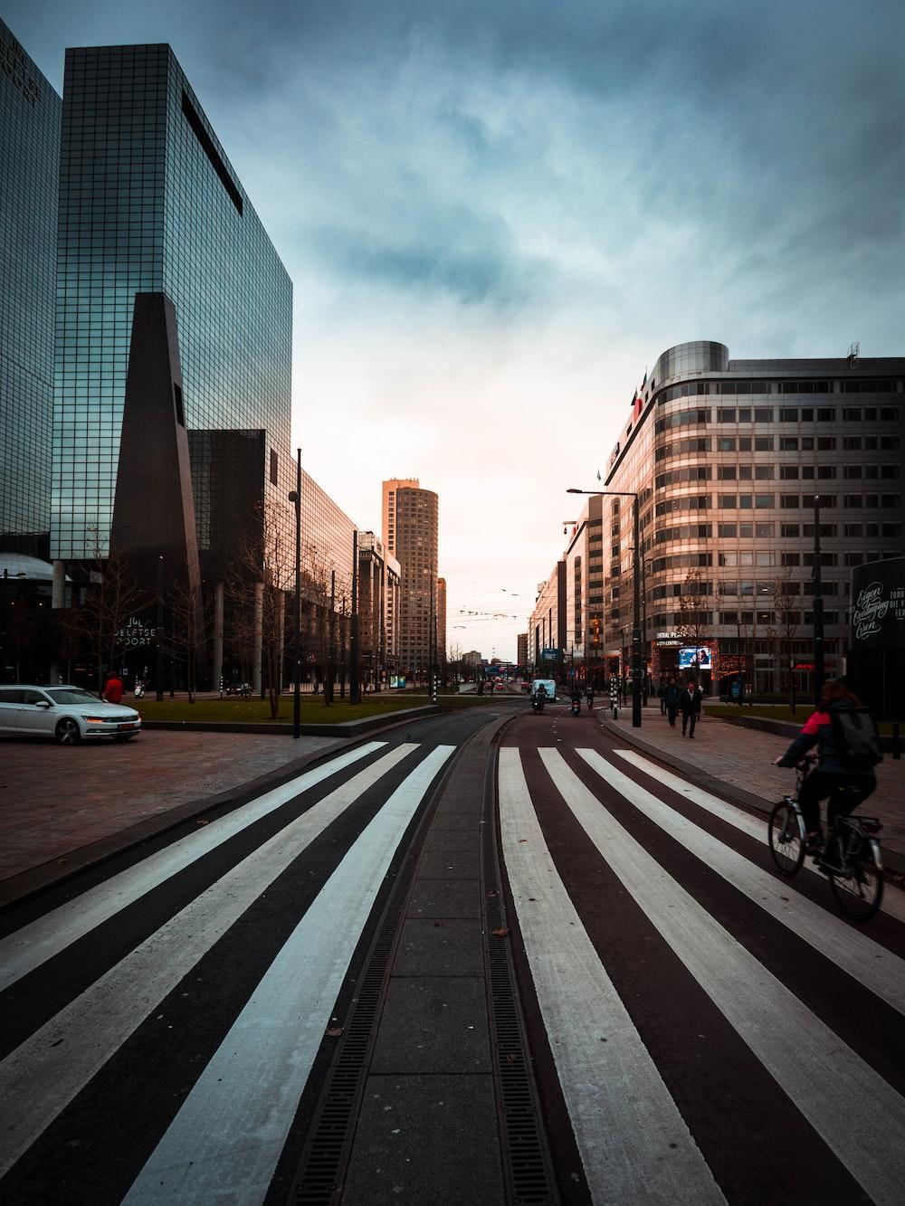 people biking and walking on road near buildings during daytime
