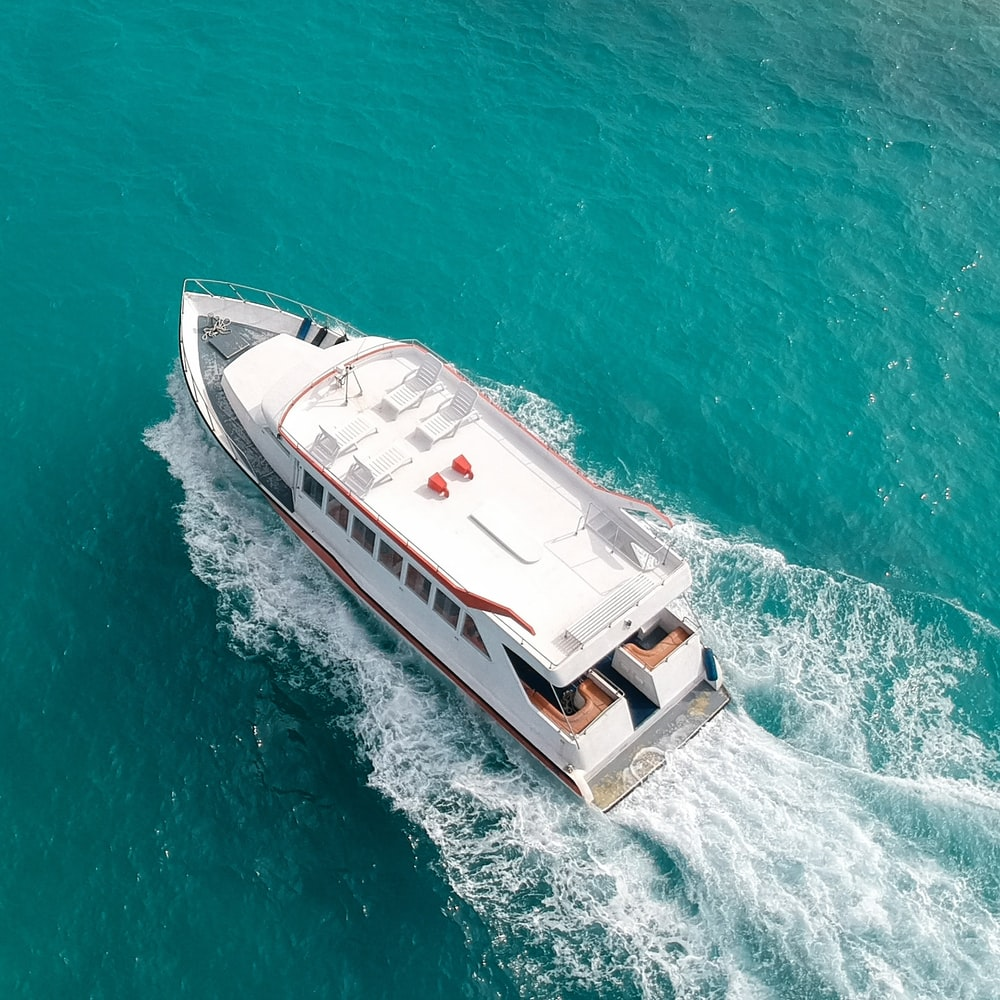 aerial photo of white and brown yacht on water