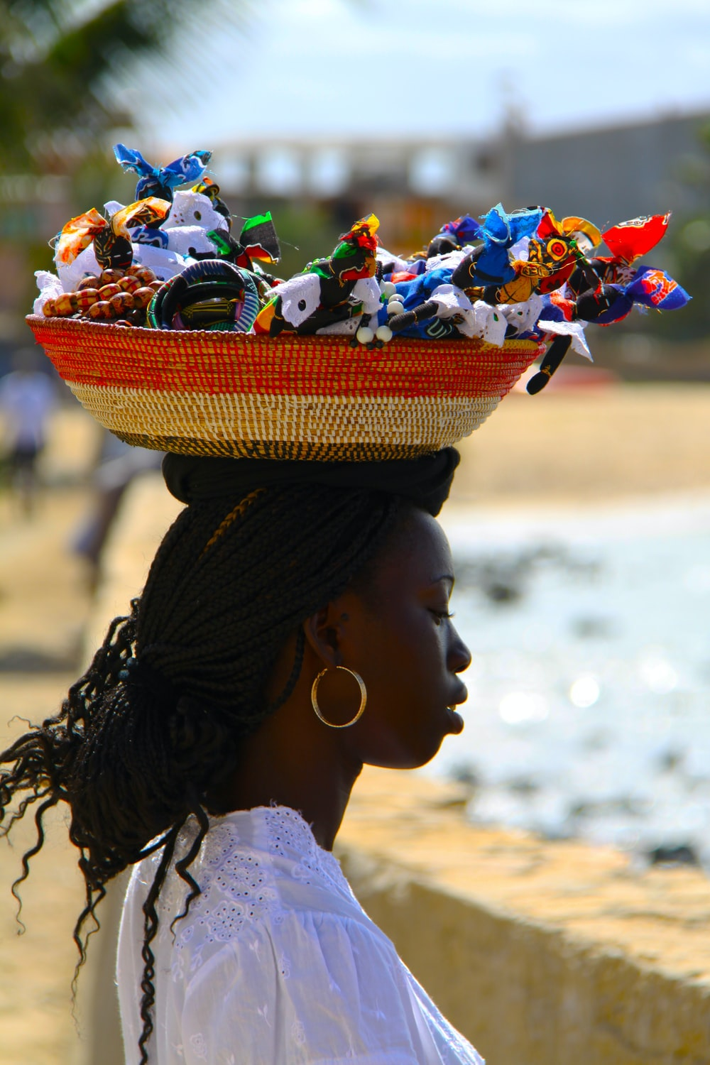 man with red and gray basket on top of her head filled with assorted dolls
