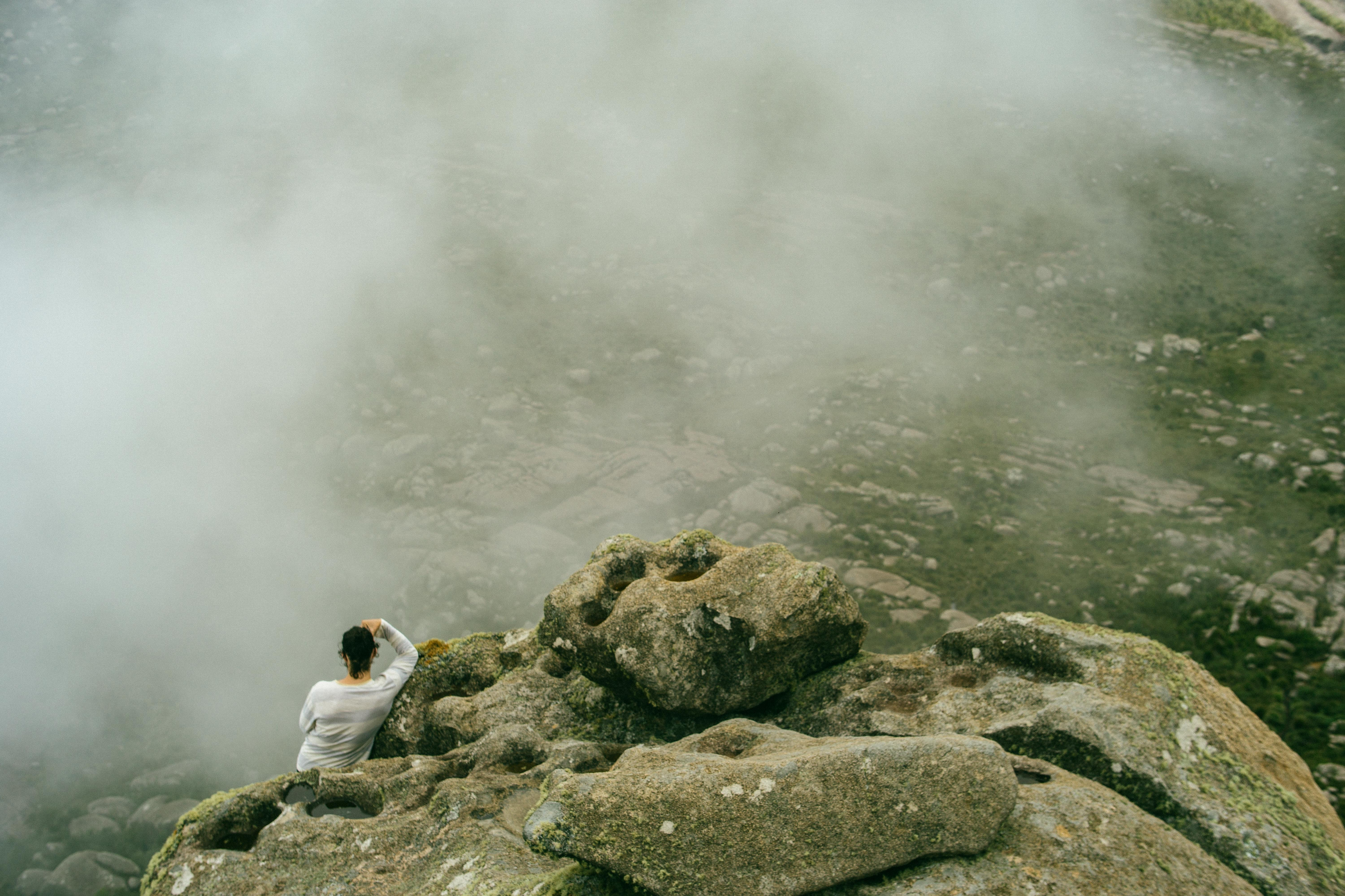 aerial photography of man sitting on peak of rock formation