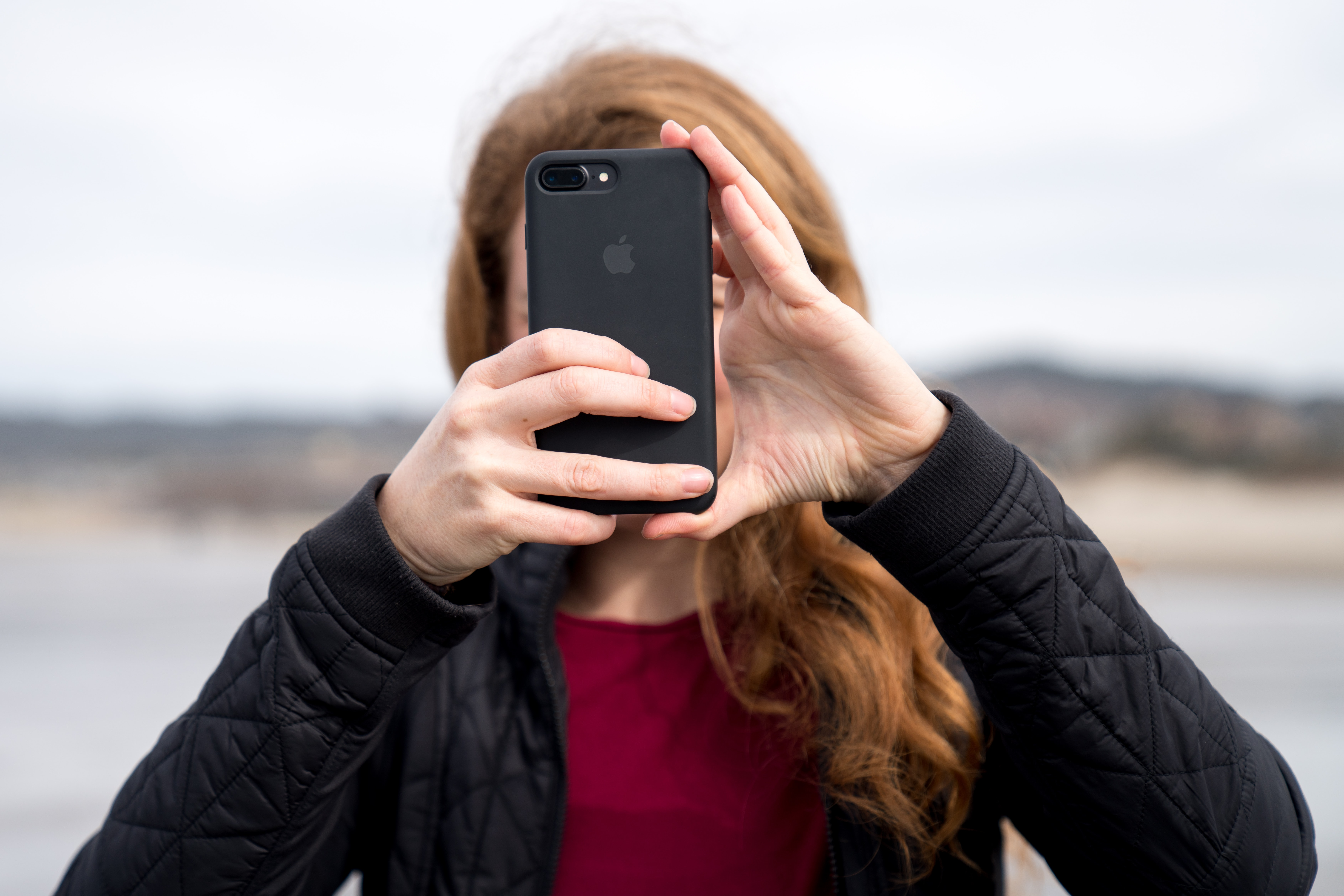 woman taking photo using black iPhone 8 Plus