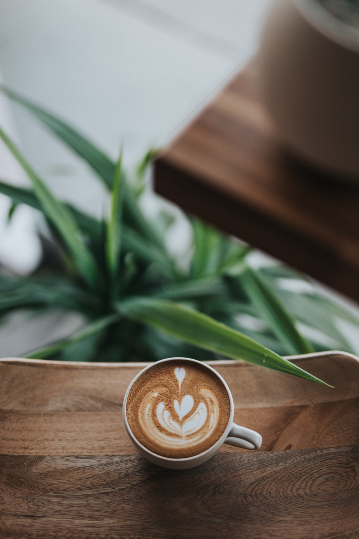 white ceramic coffee mug with coffee on table