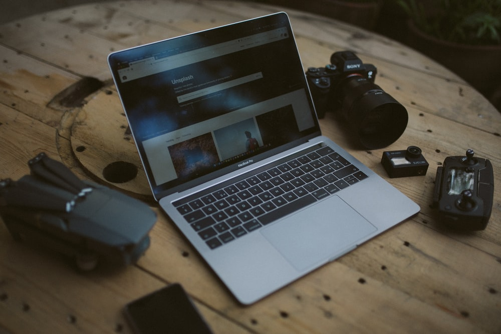 silver MacBook Air and SLR camera on table