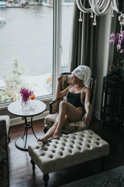 woman wearing one-piece swimsuit sitting on chair while looking outside