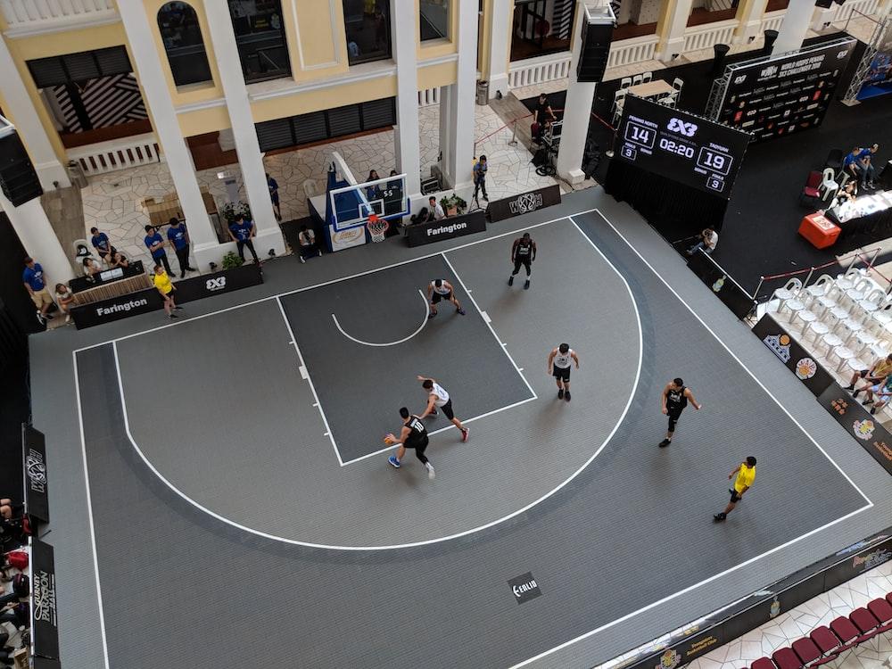 man playing basketball on gray court