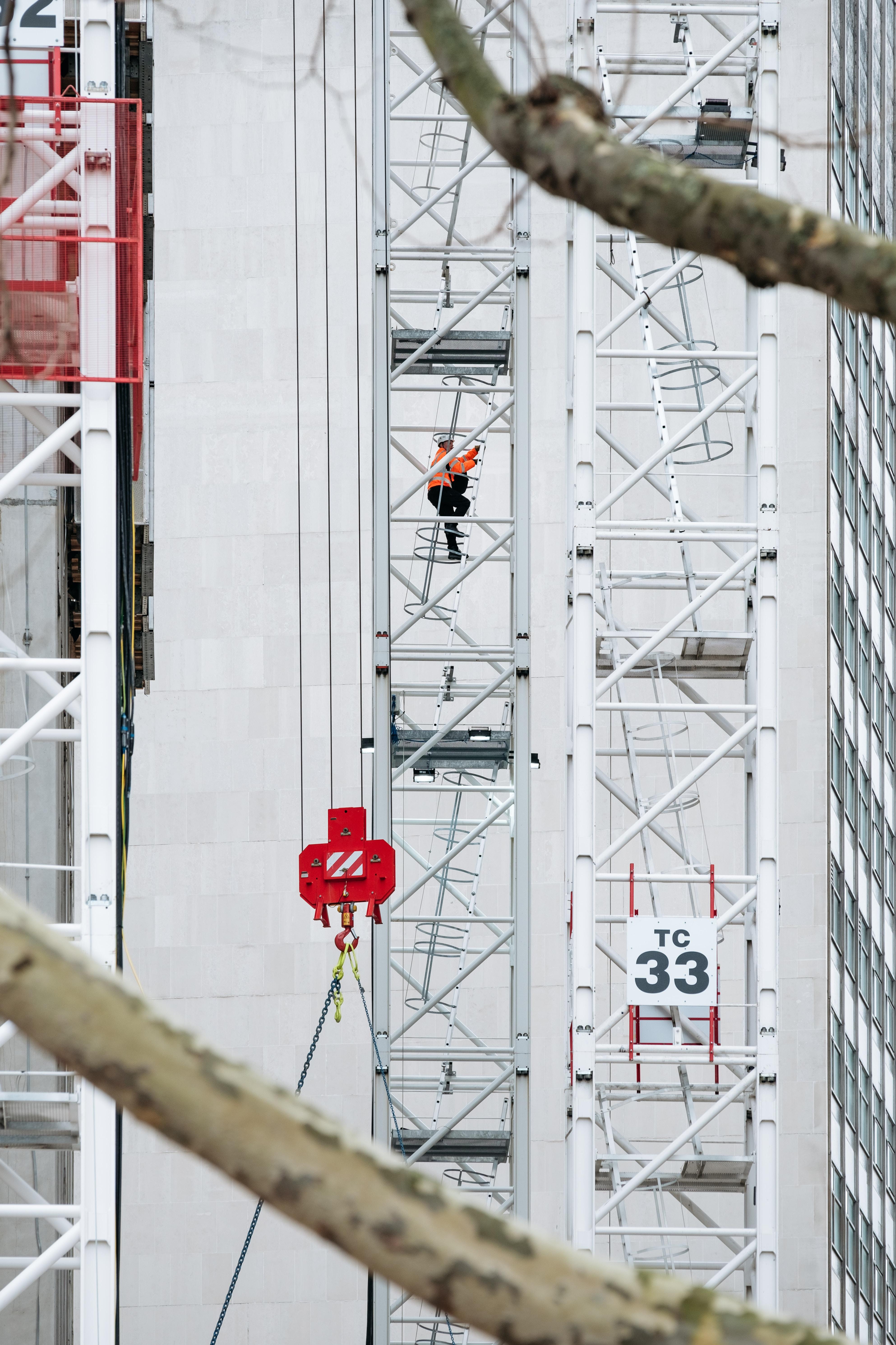 man climbing gray scaffold