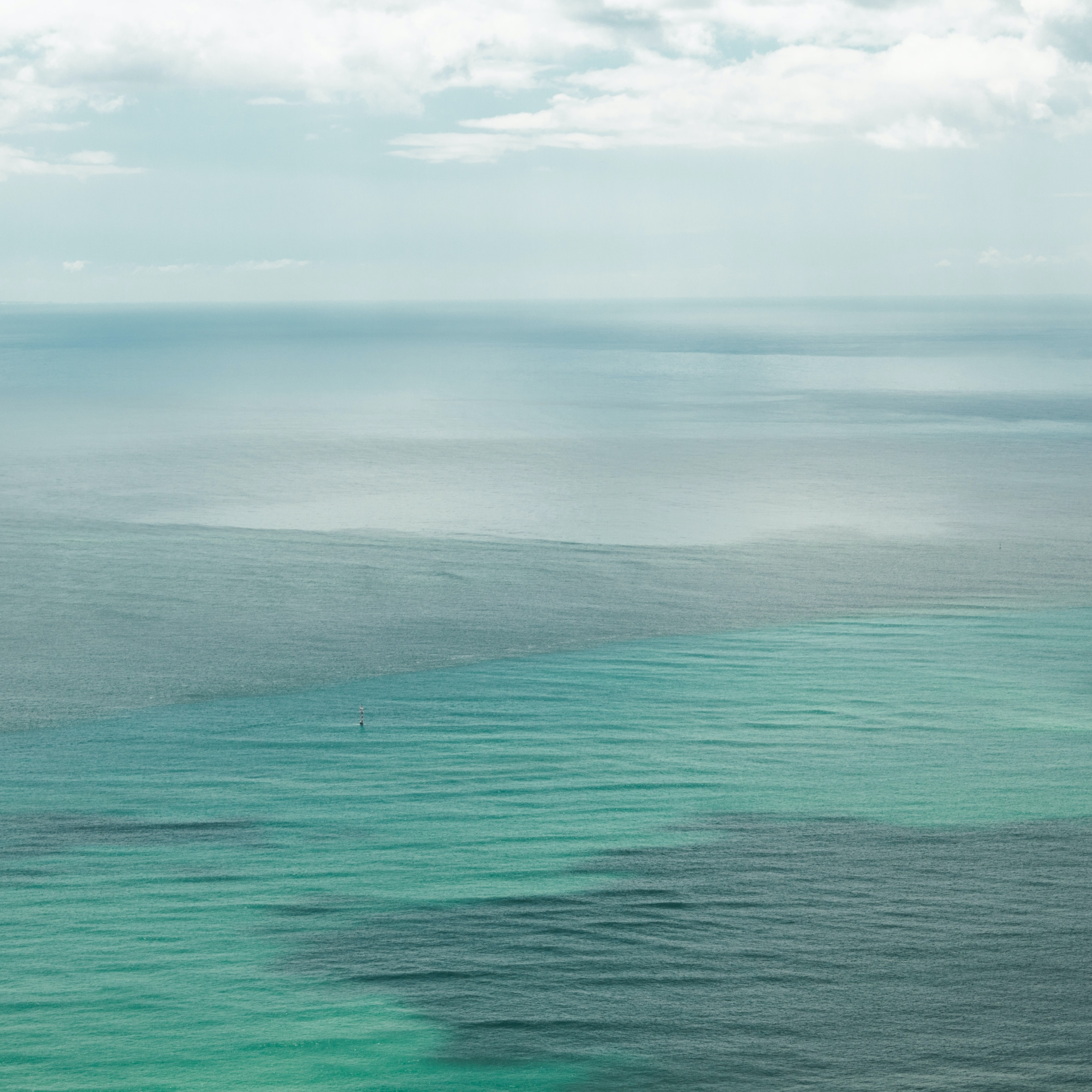 gray ocean water under white cloudy sky
