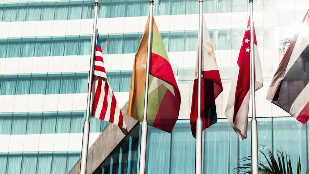 several country flags near to glass building